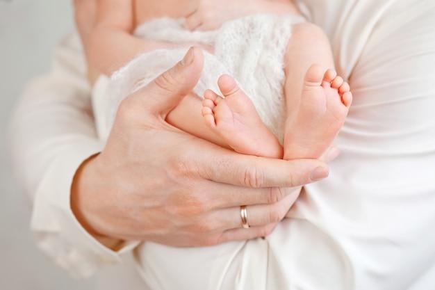 Детские ножки в руках отца. ноги крошечного новорожденного на мужских форменных руках крупным планом. папа и его ребенок. концепция счастливой семьи.