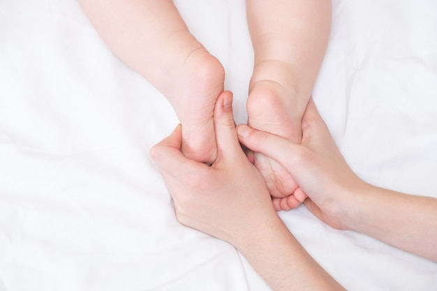 엄마의 손에 아기 발. 여성의 손 모양에 작은 신생아의 발을 닫습니다. 엄마와 그녀의 아이.