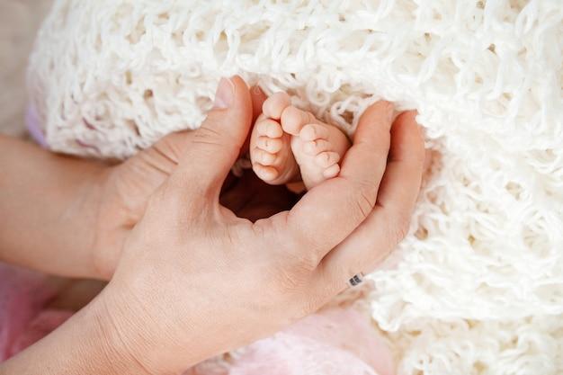 母の手で赤ちゃんの足。マタニティの美しい概念的なイメージ