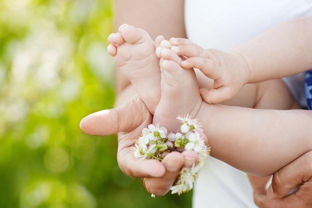母の手で赤ちゃんの足。屋外の女性の手のクローズアップに小さな子供の足。ママと彼の子供。幸せな家族の概念。親子関係の美しい概念図。