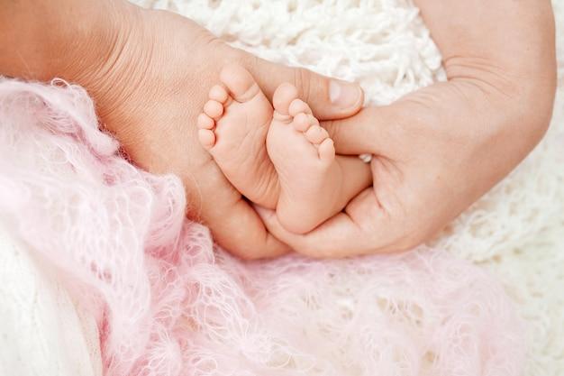 母の手で赤ちゃんの足。