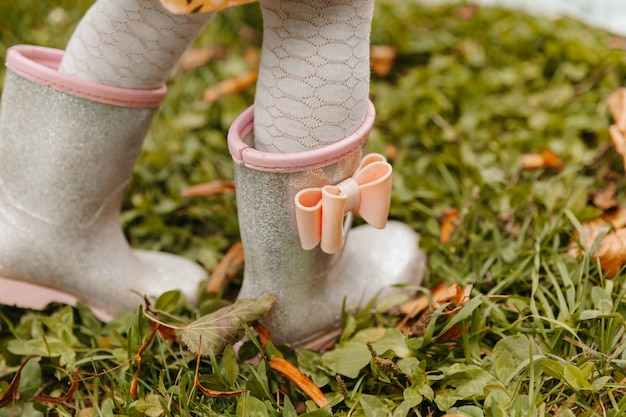 Детские ножки в резиновых сапогах заделывают. в осенний день ребенок бегает по лужам.
