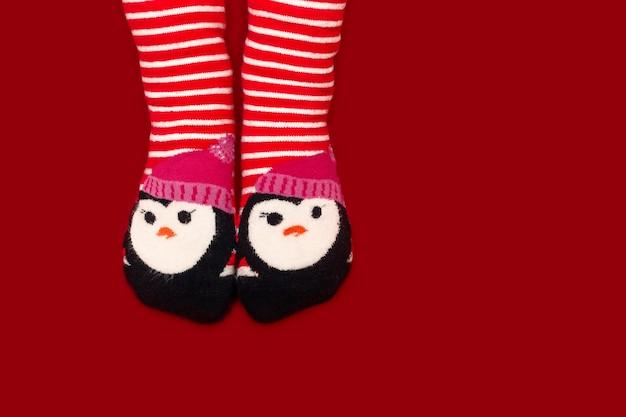 Детские ножки в полосатых красных колготках на красном фоне
