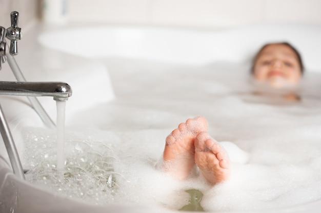 泡と泡のクローズアップでバスルームの赤ちゃんの足。白い泡の浴槽で入浴