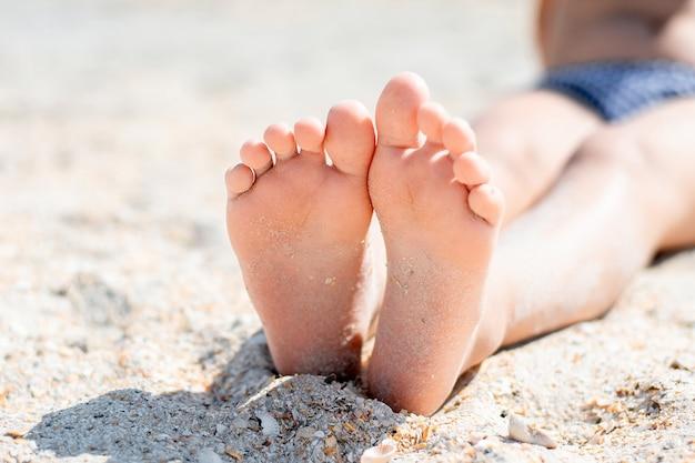 여름에 모래에 아기 발