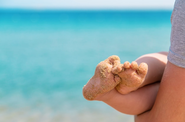 海の背景に赤ちゃんの足