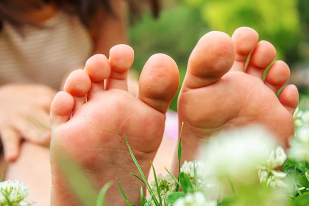 緑の芝生の上の赤ちゃんの足。セレクティブフォーカス。自然。