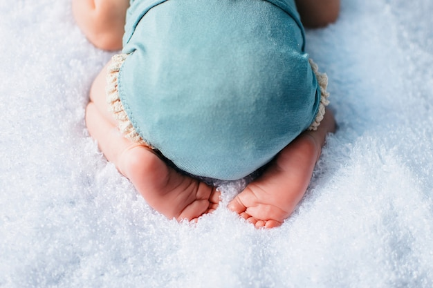 Детские ножки на белом одеяле