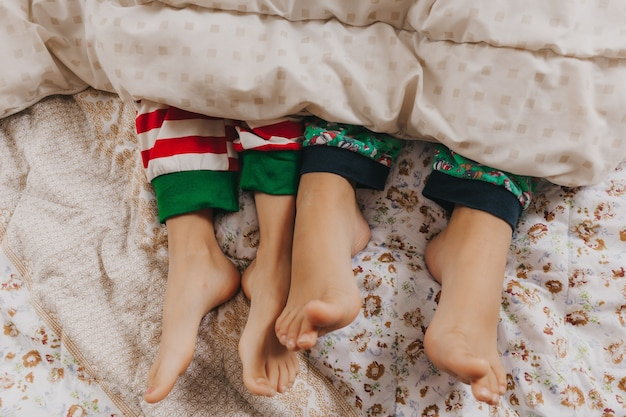 Baby feet peek out from under the blanket. two children of different ages. feet close up. concept of christmas and new year