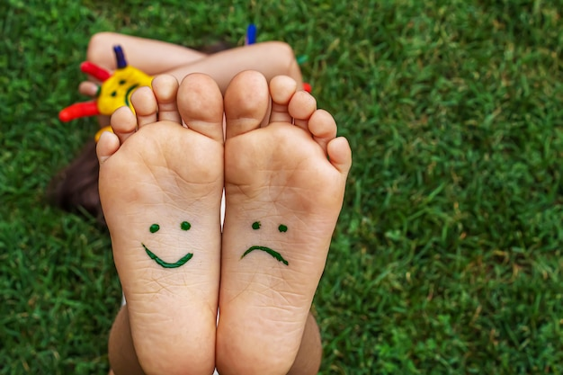 緑の芝生の上で、ペイントパターンの赤ちゃんの足が笑顔で悲しんでいます。セレクティブフォーカス。自然。