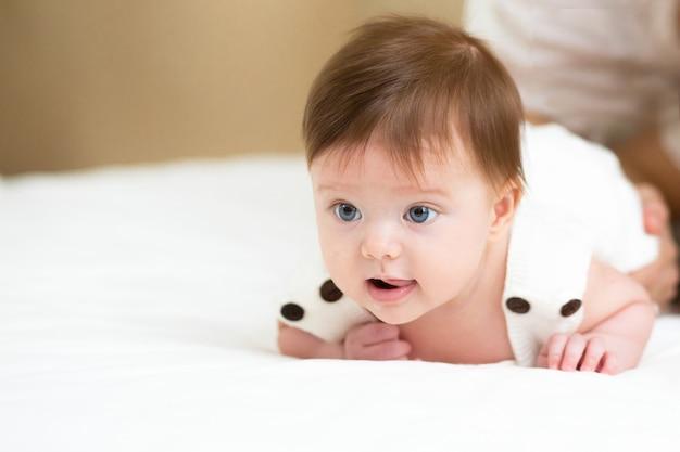 Ребенок сначала перевернет упражнение с помощью мамы. милый маленький ребенок поворачивается животом в постели