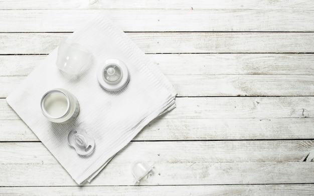 ベビーフード。小瓶に入ったベビーミルク。白い木製のテーブルの上。