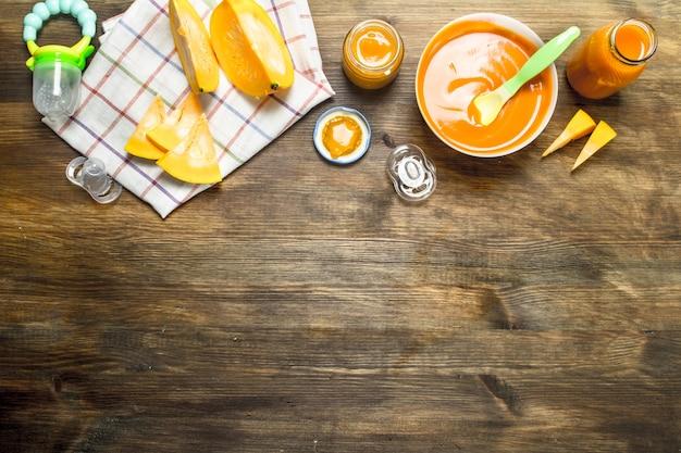 離乳食木製テーブルの上の新鮮なカボチャからのベビーピューレ