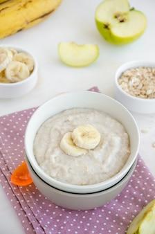 ベビーフード。明るい背景にスプーンでボウルにリンゴとバナナのスライスとクリーミーなオートミール。健康的な朝食。朝食のお粥。