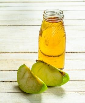 ベビーフード。リンゴからのフレッシュジュース。白い木の背景に。