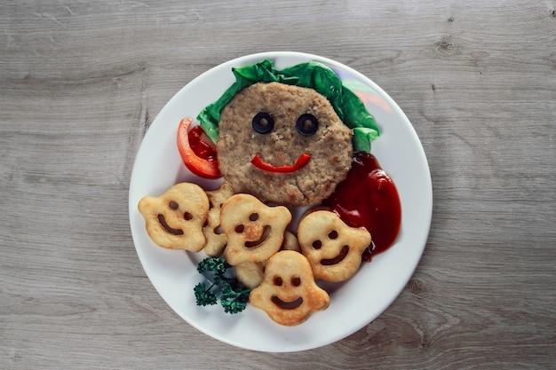 ベビーフード。白い皿に野菜とジャガイモのおやつと面白いカツレツ