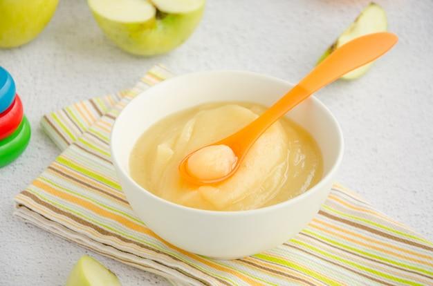 Детская еда. домашнее яблочное пюре или соус из органических яблок в миску с ложкой на светлой поверхности со свежими яблоками. горизонтальная ориентация. вид сверху. закрыть
