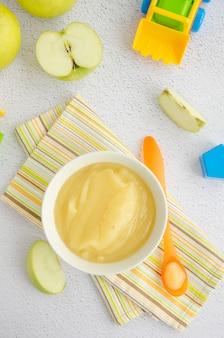 Детская еда. домашнее яблочное пюре или соус из органических яблок в миску с ложкой на светлой поверхности со свежими яблоками. вертикальная ориентация. вид сверху.