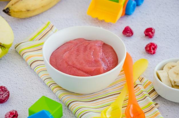 Детская еда. домашнее яблочное пюре или соус с бананом и малиной в миску. здоровая пища.