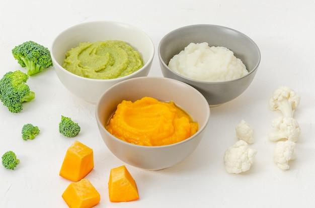 Детское питание пюре из тыквы, пюре из цветной капусты и пюре из брокколи в мисках