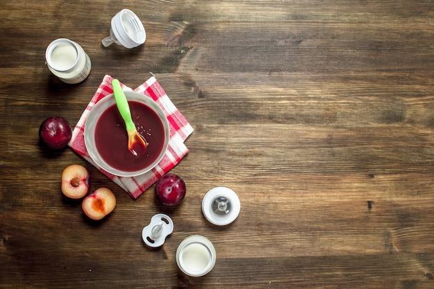 ベビーフード。新鮮なプラムのピューレにベビーミルクをボトルに入れます。木製のテーブルの上。