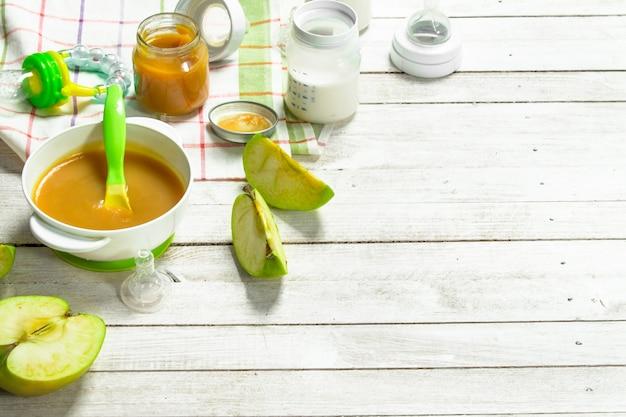 ベビーフード。青リンゴと新鮮なベビーミルクのピューレをボトルに入れます。白い木の背景に。