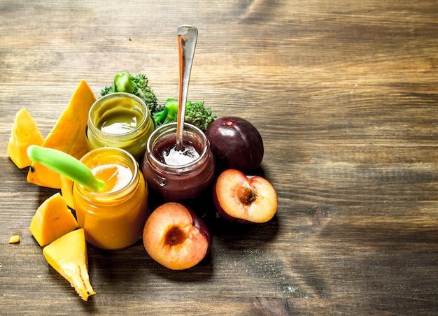 ベビーフード。果物や野菜からのさまざまなベビーピューレ。木製の背景に。