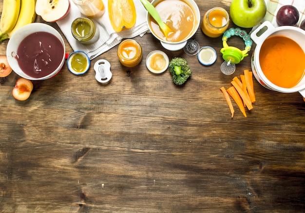 ベビーフード。果物や野菜からのさまざまなベビーピューレ。木製のテーブルの上。