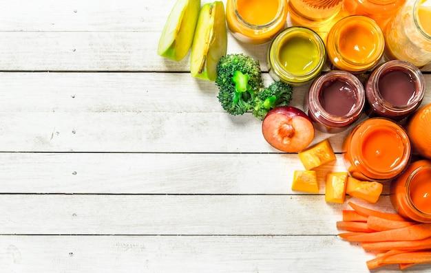 ベビーフード。新鮮な野菜や果物からのさまざまな赤ちゃんのピューレ。白い木の背景に。