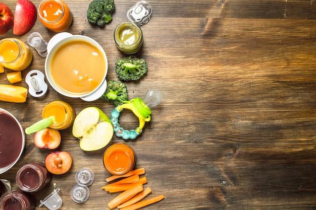 ベビーフード。果物や野菜のさまざまなピューレ。木製の背景に。