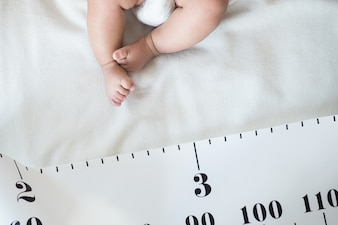 Baby Foot and measuring tape: concept of baby growth, height, development