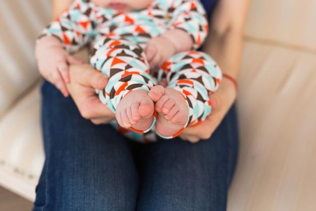 여성 손에 아기 발, 클로즈업입니다. 귀여운 꼬마 다리. 출산, 사랑, 보살핌, 새로운 삶의 개념.