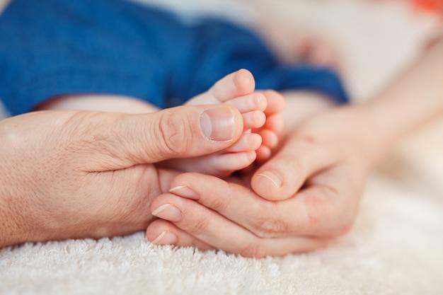 母の手で赤ちゃんの足
