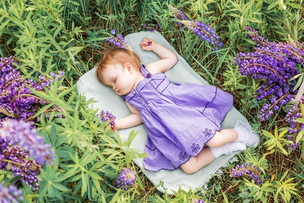 Baby girl 1 year old sleeping in nature among flowers