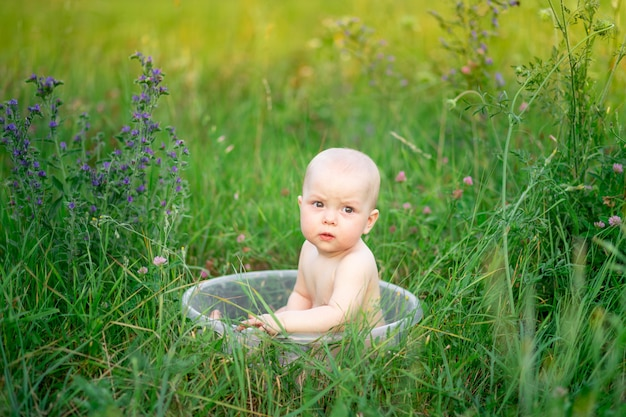 Baby girl 10 months old bathes in a basin in the grass in the summer