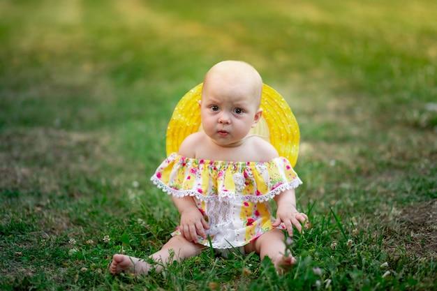 Девочка 10 месяцев сидит на траве летом в желтом платье
