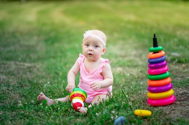 여름에 풀밭에 앉아서 피라미드를하고 10 개월 된 아기 소녀, 어린이의 조기 발달, 야외 게임
