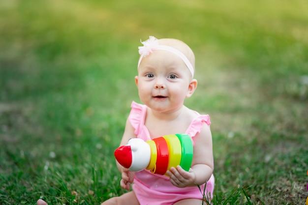 夏の草の上に座って、ピラミッドを遊んで10ヶ月の女の赤ちゃん