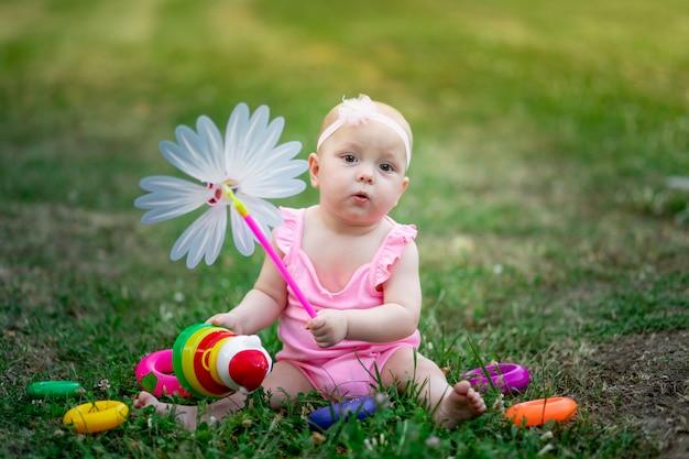 Девочка 10 месяцев сидит на траве летом и играет с проигрывателем