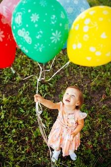 2〜3歳の女の赤ちゃんが屋外の風船を保持しています。誕生日会。子供時代。幸福。