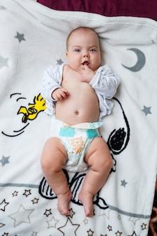 生後3ヶ月の女の赤ちゃんがベッドに横たわっています。おむつの服のない赤ちゃん