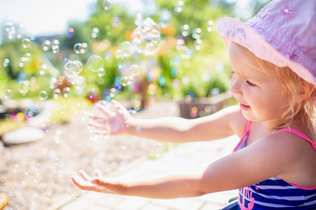 Baby girl 3 year old in a pink hat and blue stripped swimsuit having bath at backyard and playing with bubbles.