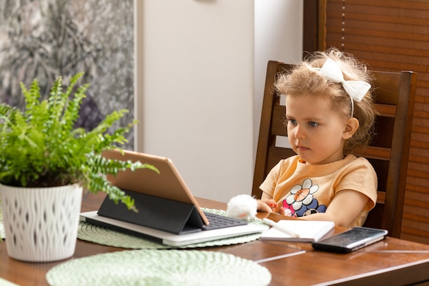 Baby girl 3 years old with curly hair is sitting at table. online homeschooling with tablet at home.