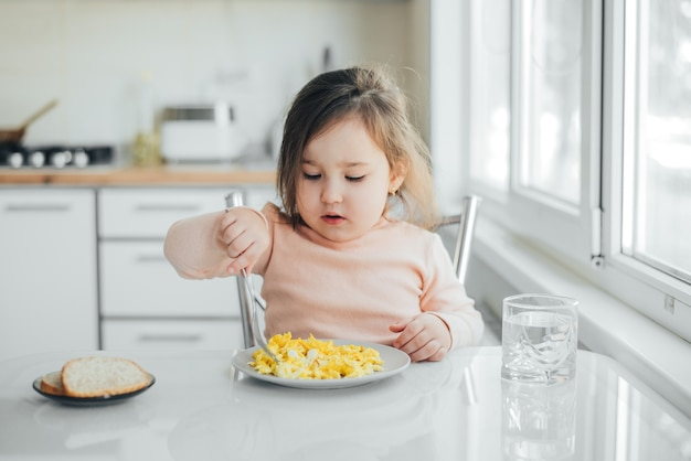 Baby girl in the afternoon in the white light kitchen in a pink sweater eating an omelet
