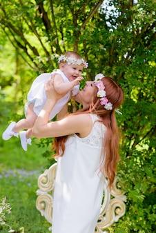 花の花輪と春の庭で白いドレスの赤ちゃんの女の子と母