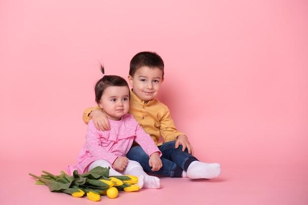 ピンクのスタジオの背景に女の赤ちゃんと兄の男の子