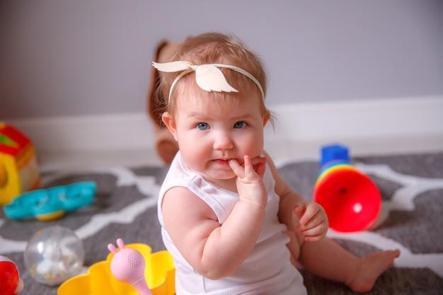 Девочка дома сидит на полу, играя с игрушками