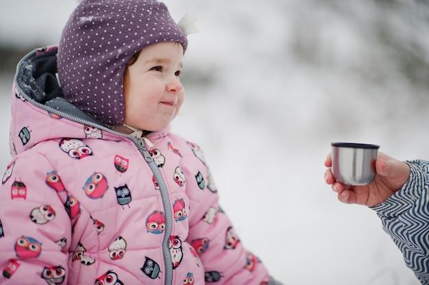 冬の日の女の赤ちゃんは熱いお茶を飲みます。