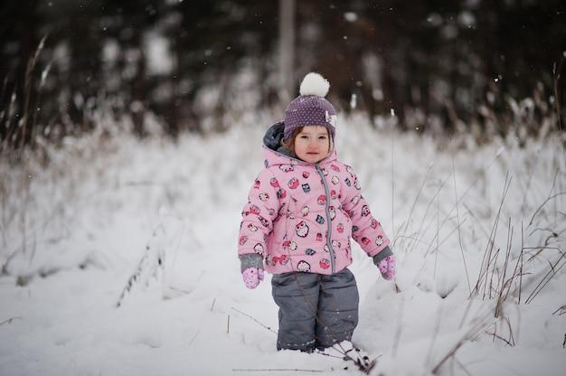 冬の日の女の赤ちゃん。雪の降る寒い日に公園を散歩。