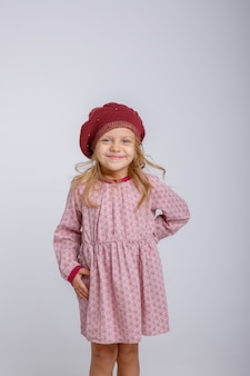 Baby girl in autumn beret on grey background